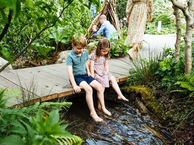 Older siblings Prince George, five, and Princess Charlotte, four, are seen dangling their bare feet over a stream of water as the family look happy and relaxed on a day out near their west London home.