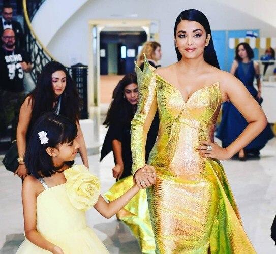 Cô bé Aaradhya trầm trồ trước bộ đầm như bông sen vàng lộng lẫy của mẹ.
