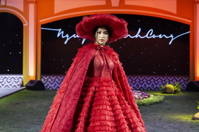 Tiểu Vy xuất hiện lộng lẫy trong chiếc váy cưới gam màu đỏ rực rỡ. Áo choàng và tùng váy được tạo khối và xếp layer bồng bềnh, mang đến vẻ đẹp ấn tượng cho người đẹp.