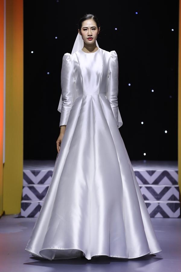 Váy lụa trắng cắt may theo hướng tối giản, nhấn nhá tay phồng cổ điển, phù hợp cô dâu theo đuổi phong cách thanh lịch, sang trọng.