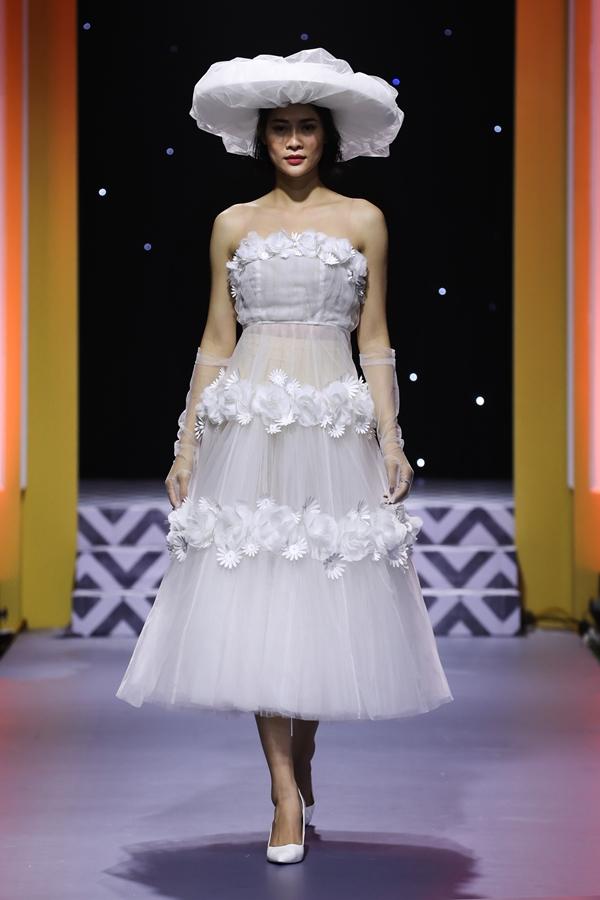 Nhiều bạn gái yêu thích váy cưới có chiều dài vừa phải, tạo cảm giác nhẹ nhàng và thoải mái trong ngày trọng đại. Họa tiết hoa 3D đính kết trên nền vải voan tạo điểm nhấn. Khăn voan truyền thống được thay thế bằng mũ đội đầu lạ mắt.