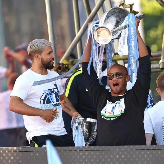 Kompany giương cao Cup vô địch Premier League bên cạnh Sergio Aguero, người can ngăn anh đừng sút bóng trong trận thắng 1-0 trước Leicester City hôm 6/5. Ảnh: Sun.