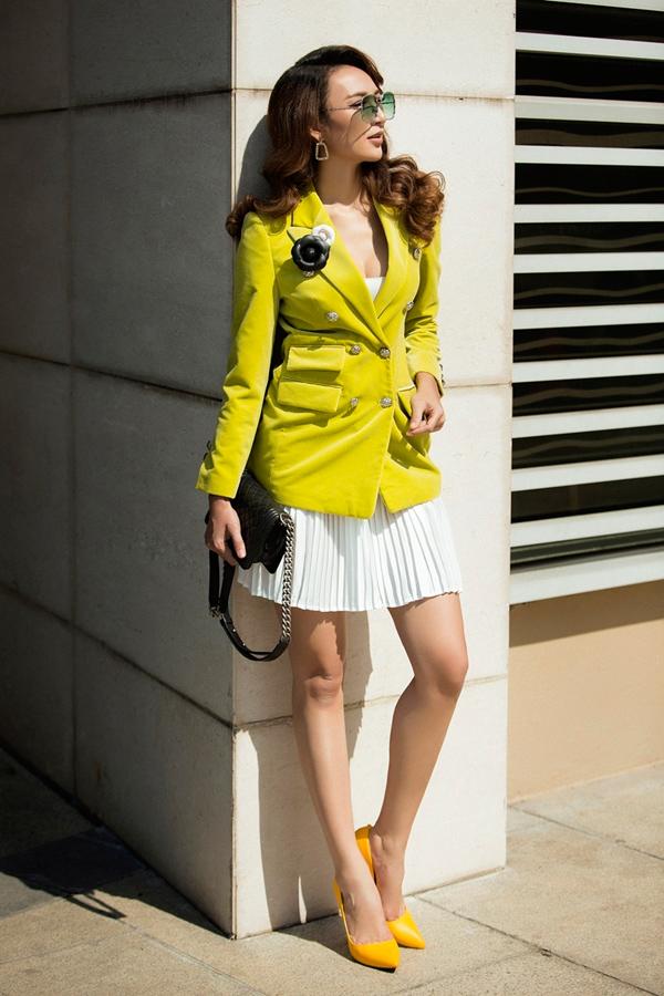 Khi muốn thể hiện phong cách thời thượng hơn, mỹ nhân 8X diện váy ngắn dập ly xòe nhẹ nhưng không quên bổ sung vẻ thanh lịch bằng blazer cài cúc.