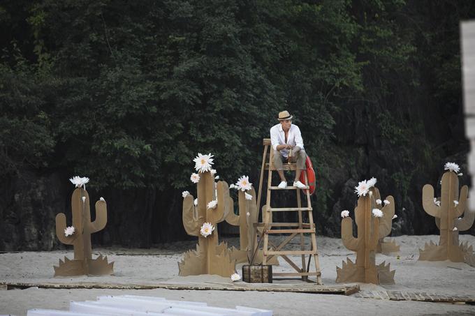 Người mẫu Long Lê xuất hiện như một khách viễn du cho phần mở màn bộ sưu tập của Nguyễn Tiến Truyển. Trên bãi cát dài sát sàn catwalk, giấy tái chế được tận dụng để mang tới tạo hình xương rồng nở hoa.