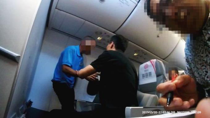 Người đàn ông mặc áo xanh gây rối trên chuyến bay của Fuzhou Airlines hôm 20/5. Ảnh: AsiaWire.