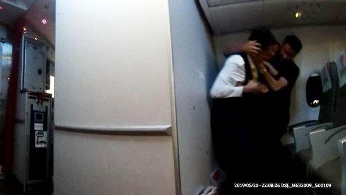 Nam hành khách nổi giận và tóm chặt tóc của một nam tiếp viên trên máy bay. Ảnh: AsiaWire.