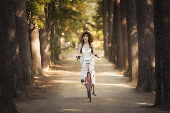 Nữ ca sĩ mặc váy dây gợi cảm, thảnh thơi đạp xe trên con đường rợp bóng cây xanh ở đảo Nami. Đây từng là bối cảnh củabộ phim truyền hình Hàn Quốcnổi tiếngBản tình ca mùa đông.