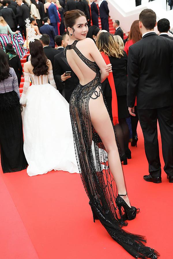 Kết  cấu hai tà váy dài xẻ cao lên đến tận phần hông giúp Ngọc Trinh khoe trọn vẹn đôi chân dài cũng như hình thể tựa như một nữ thần sắc đẹp.