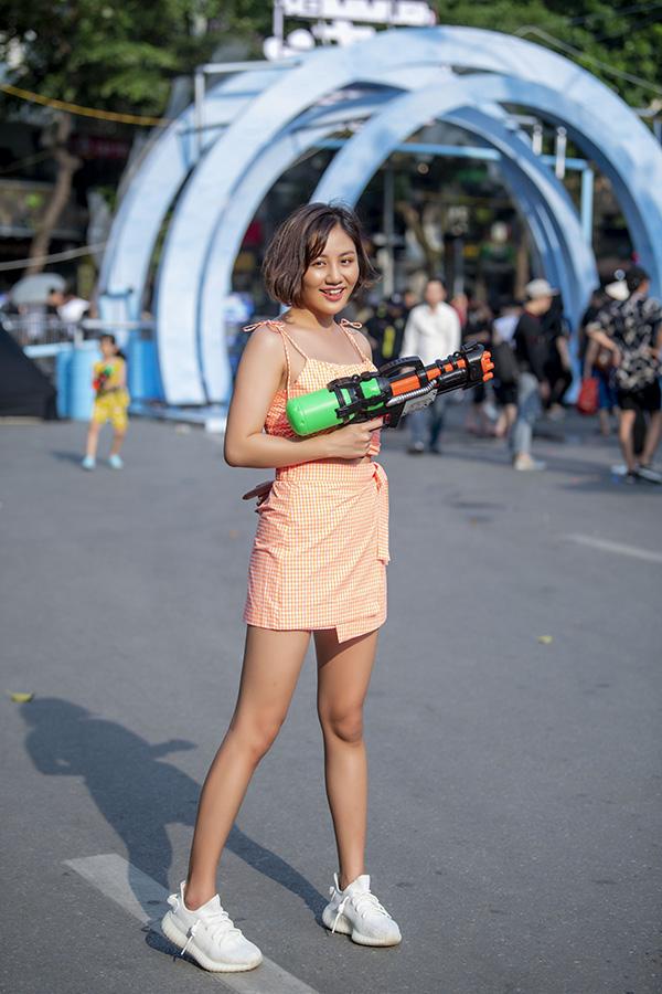 Nữ ca sĩ mặccroptop kẻ caro màu cam đồng điệu với chân váy kết hợp cùng giày sneaker để hoàn thiện vẻ ngoài năng động khi tham gia các trò chơi ngoài trời.