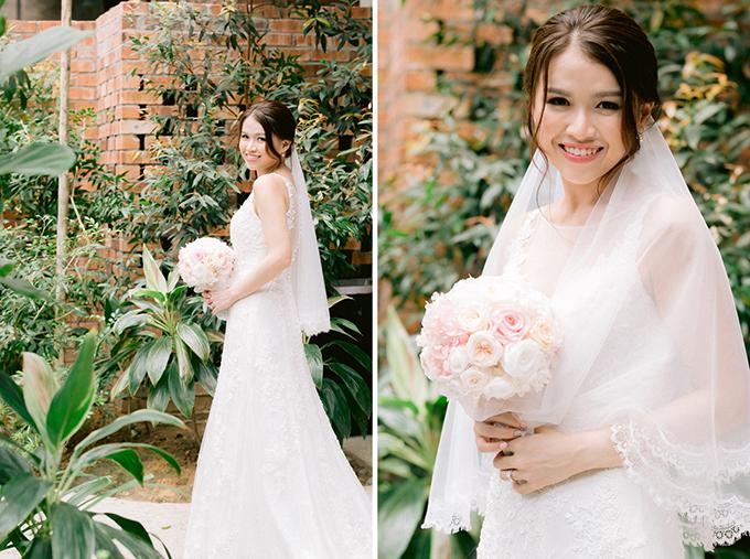 Cô dâu Elisha chọn diện đầm cưới dáng chữ A đính ren, lúp cưới ngắn và hoa cầm tay màu phớt hồng.