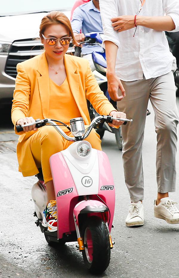 Thay vì ngồi xe hơi, Mỹ Tâm tới buổi ký tặng đĩa bằng chiếc xe điện mini fan tặng cô. Hình ảnh nữ ca sĩ mặc vest vàng, mang giầy thể thao lái xe mini khiến người hâm mộ thích thú.