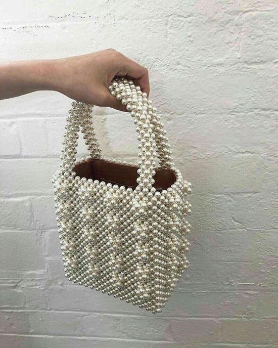 Hạt giả ngọc trai được đan kết công phu để mang tới các mẫu túi xách tay phom dáng vuông vức. Túi phom cỡ trung là sản phẩm được yêu thích nhiều nhất.