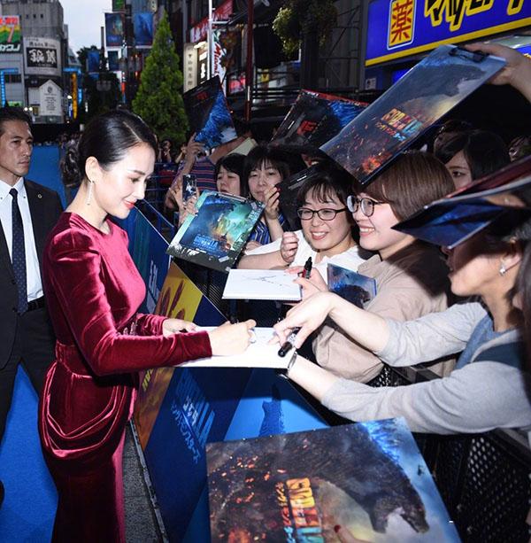 Chương Tử Di ký tặng người hâm mộ tại buổi họp báo. Trước đó, cô cũng rất được hoan nghênh khi ra mắt Chúa tể Godzilla ở Mỹ.