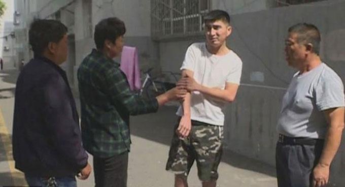 Tonik (áo trắng) ôm cánh tay bị thương sau khi đỡ bé trai rơi từ ban công tầng 4 ở thành phố Y Ninh, Tân Cương hôm 23/5. Ảnh: Asiawire.