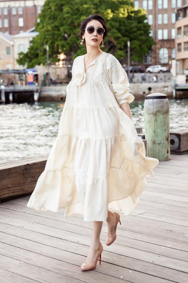 Người đẹp sinh năm 1976 duyên dáng trong mẫu váy bay bổng. Để trang phục trơn màu trở nên độc đáo hơn, Đỗ Mạnh Cường chọn cách xử lý chất liệu theo đường cắt ngang và nhún xếp nhẹ nhàng.