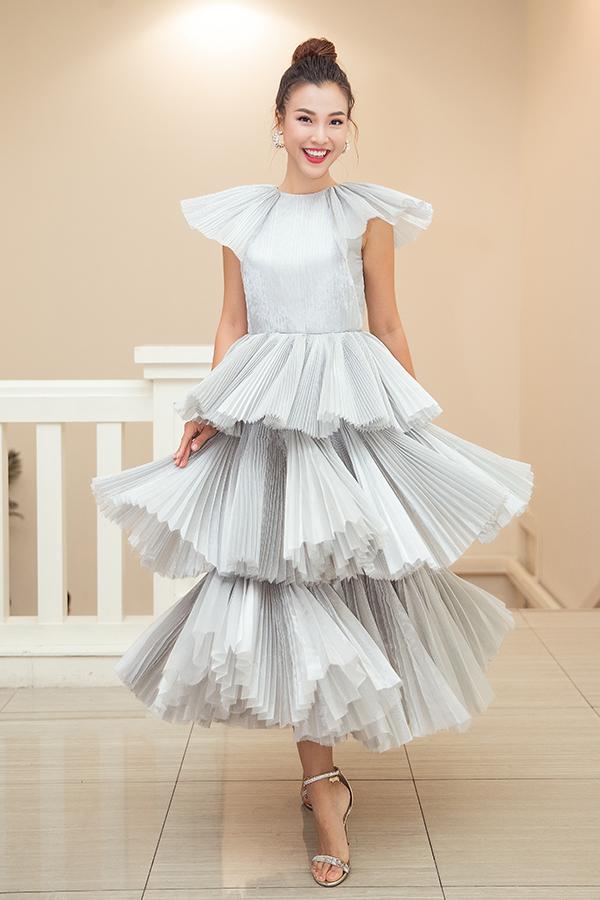 Nữ diễn viên - MC tung váy chụp hình khi đến dự sự kiện. Chiếc váy xếp tầng màu trắng và kiều tóc búi cao khiến cô vừa điệu đà vừa trẻ trung.
