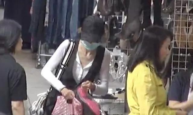 Trương Mạn Ngọc tay xách nách mang ở khu chợ bình dân.