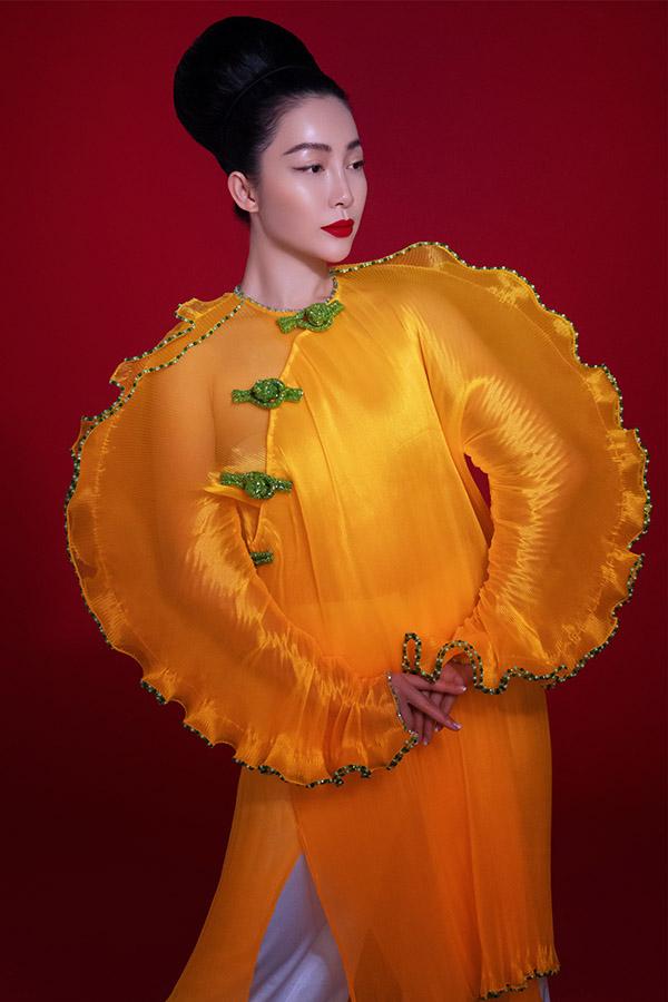 Linh Nga đắt show làm mẫu chụp ảnh áo dài. Diễn viên múa trông lạ lẫm khi mặc trang phục màu cam xuyên thấu, hai tay áo thiết kế phồng to.