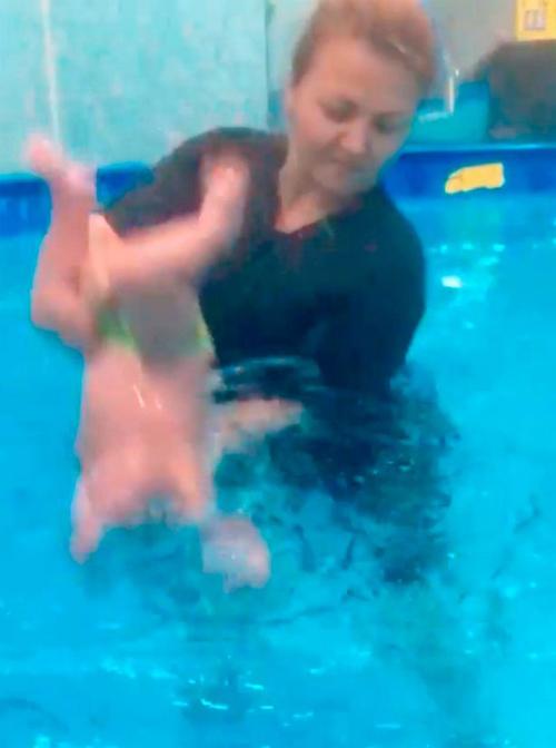 Elena dốc đầu một em bé xuống nước trong giờ dạy của mình. Ảnh: east2west.
