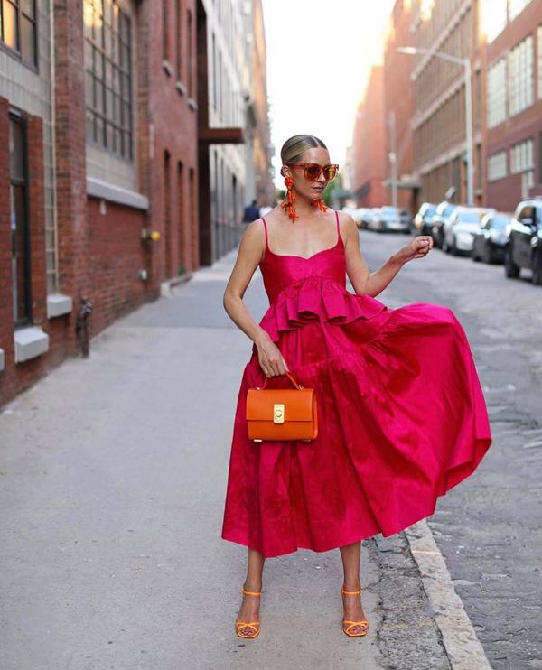 Tông hồng cánh sen và cam nóng bỏng được phối hợp cùng nhau trên set đồ gồm váy áo hai dây, sandal và túi xách tiệp màu.