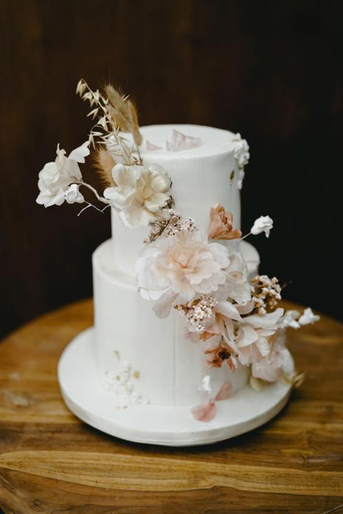Chiếc bánh cưới hai tầng màu trắng ngà được thiết kế trang nhã, có hoa tô điểm.Bánh có vị chanh mật ong truyền thống.