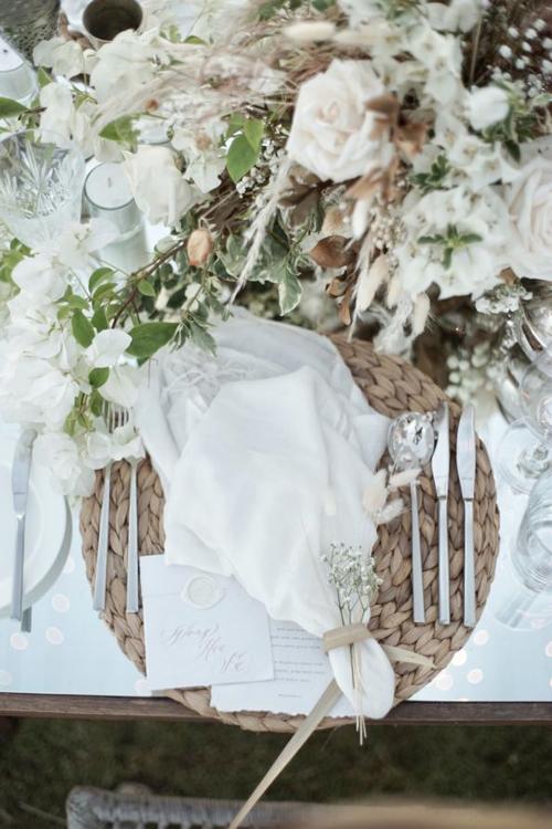 Ở trên bàn tiệc được tô điểm với hoa tươi, khăn ăn và bộ dao nĩa trắng bạc dành cho khách mời.