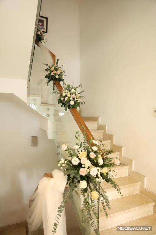 Khu vực cầu thang dẫn lên phòng cô dâu cũng được trang trí hoa tươi, lá mimosa.