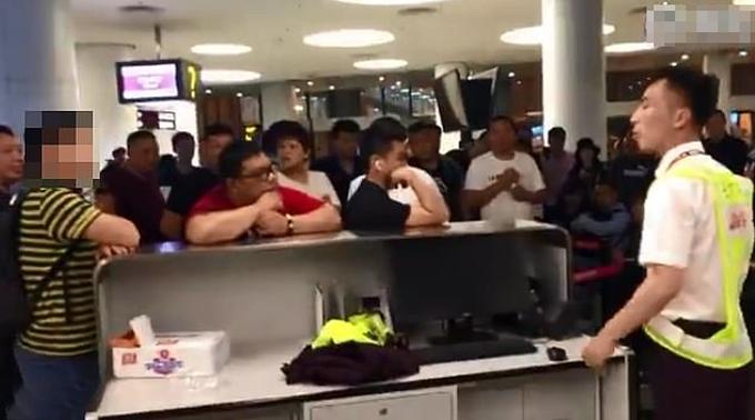 Nam hành khách (áo vàng kẻ đen) bắt nhân viên sân bay quỳ để xin lỗi hành khách bị muộn giờbay từ Trịnh Châu tới Thâm Quyến hôm 25/5. Ảnh: Weibo.