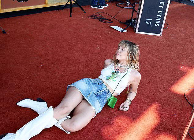 Người đẹp vừa kết hôn 6 tháng với tài tử Liam Hemsworth quyết định đổi khác với dòng nhạc mới trong đĩa She Is Coming. Cô cũng trở lại năng động và trẻ trung sau một thời gian thử sức với kiểu nhạc pop kết hợp đồng quê.