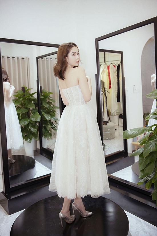 Ngọc Trinh khá quan tâm đến thiết kế váy đính pha lê mới nhất của Đỗ Long. Cuối cùng, một thiết kế váy cúp ngực tông trắng, khoe vóc dáng nuột nà được lựa chọn. Chiếc váy tôn lên đường cong của nữ diễn viên.