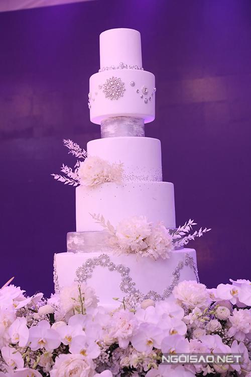 Bánh cưới của uyên ương cũng mang sắc trắng và được tô điểm với những loại hạt lấp lánh, hoa tươi.