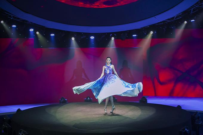 Ngay khi vừa xuất hiện, người đẹp sinh năm 1994 gây bất ngờ với những màn tung váy đẹp mắt kết hợp những động tác múa. Màn hình LED có sự thay đổi từ sắc xanh sang đỏ rực kết hợp với âm thanh dồn dập tạo hiệu ứng cho phần trình diễn.
