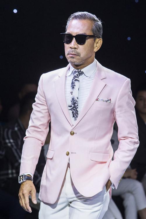 Fashionisto Thuận Nguyễn diệnsuit jacketmang sắc hồngtrẻ trung cùng quần trắng, giúp ăn gian tuổi của tân lang. Bộ trang phục mang phong cách Italy, được làm từ chất liệu len cao cấp, có độ mỏng, nhẹ và cầu vai có đệm mỏng.