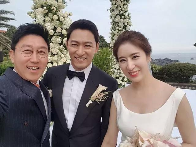 Vợ chồng cặp sao rạng rỡ bên các khách mời trong ngày vui. Vợ của Joo Jin Mo là một bác sĩ, cô nổi tiếng vì ngoại hình xinh đẹp tự nhiên.