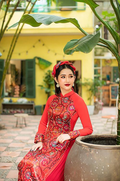 1. Áo dài gấm đỏMẫu áo có họa tiết thêu hoa ban tinh tế trước ngực, làm cho vòng eo của nàng dâu trở nên nhỏ gọn.