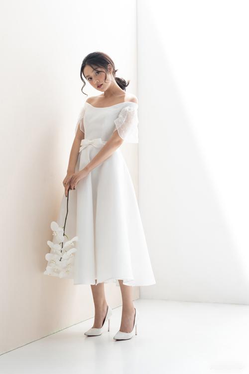 3. Váy trễ vai, nơ ở eoChiếc váy tea-length có chiều dài chạm giữa bắp chân. Phom dáng váy có thân áo ngắn, chít eo đem lại vẻ ngoài thanh lịch, cổ điển, làm toát lên sức sống tươi trẻ của nàng dâu.