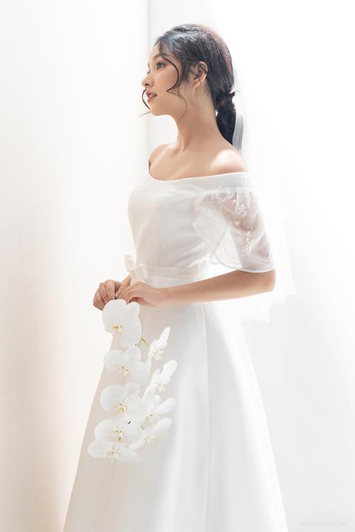 Bộ đầm làm lộ đôi vai và xương quai xanh quyến rũ của cô dâu. Chi tiết tay điểm họa tiết hoa nhỏ li ti làm tổng thể bộ đầm thêm phần tinh tế và lôi cuốn.