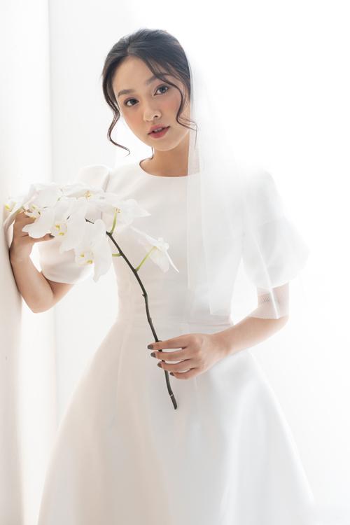 Đầm tối giản không chú trọng vào đính kết mà tập trung xử lý chất liệu, phom dáng sao cho toát lên thần thái, cá tính riêng biệt của cô dâu, giúp người đối diện tập trung ánh nhìn vào tân nương.