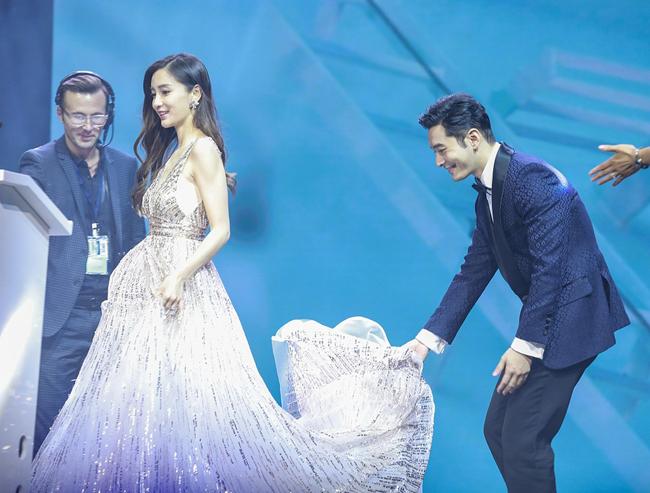 Trên sân khấu, Hiểu Minh ân cần nâng váy cho bà xã. Hiểu Minh và Angelababy kết hôn năm 2015, sau đó sinh con đầu lòng năm 2017. Cặp đôi từng có một đám cưới thế kỷ, được cả bạn bè trong giới lẫn khán giả ngưỡng mộ vì sự hoành tráng, xa hoa.