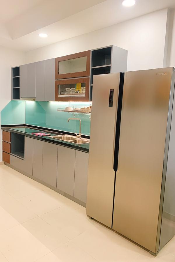 Bếp có diện tích rộng rãi. Phần tủ được Phương Hằng dán lại từ màu trắng sang xám, tạo cảm giác ấm cúng cũng như ton-sur-ton với tủ lạnh.