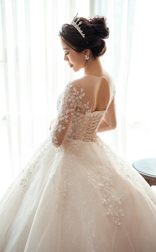 Đằng sau lưng váy là khoảng hở giúp nàng dâu khoe khéo tấm lưng thon gợi cảm.Bộ đầm có dây buộc phía sau giúp định hình phom dáng, siết vòng eo con kiến từ 10-12 cm.
