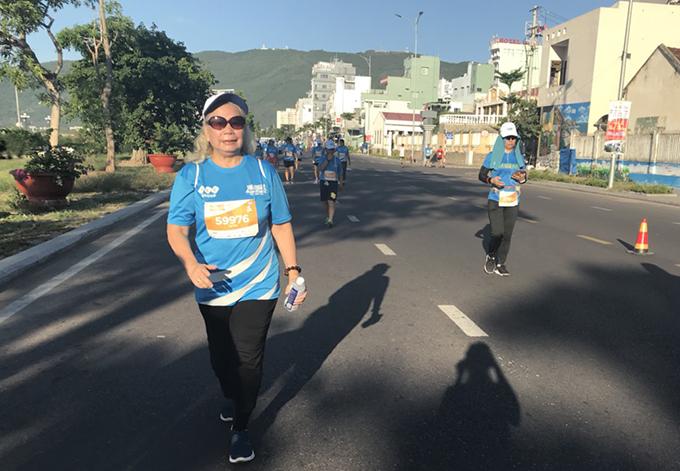 Bà Tâm vui vẻ vừa chạy vừa giao lưu với các vận động viên khác.
