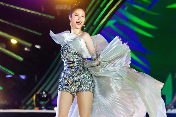 Đông Nhi tỏa sáng như vì sao bởi trang phục ánh bạc lấp lánh. Kết hợp cùng body suit trang trí cánh hoa 3D là phần tùng váy ánh kim bay bổng.