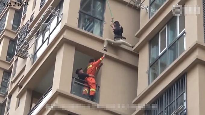 Cô gái đu dây xuống từ gờ tầng 6 khi được lính cứu hỏa giải cứu ở Hoài An, Giang Tô, Trung Quốc hôm 31/5. Ảnh:ChengduBusiness Daily.