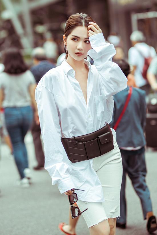 Vấn diện mẫu áo sơ mi trắng của nhà mốt Balenciaga nhưng Ngọc Trinh lại chọn short jeans dáng ôm để mix đồ. Biker short cũng là một trong những xu hướng được yêu thích nhất ở mùa thời trang 2019. Ngọc Trinh sớm cập nhật mốt này để có phong cách street style không thu kém dàn ngôi sao, fashionista thế giới.