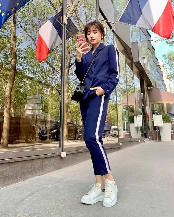 Hari Won trẻ trung cùng suit phối đường kẻ sọc phối tông xanh - trắng cuốn hút. Trào lưu diện suit cùng các mẫu giầy thể thao cũng được bà xã Trấn Thành áp dụng hiệu quả.