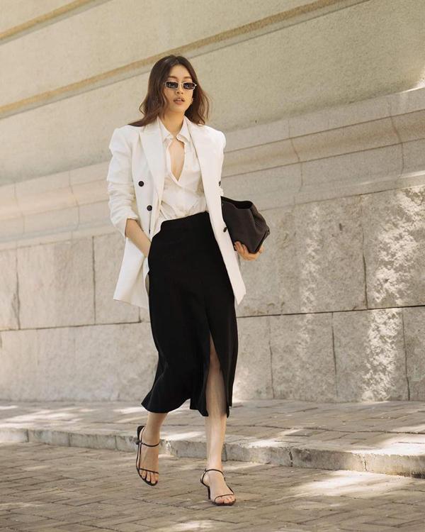 Hai gam màu trắng đen được Lệ Hằng phối hợp một cách hoàn hảo cho set đồ gồm sơ mi, vest và chân váy tông màu tương phản.