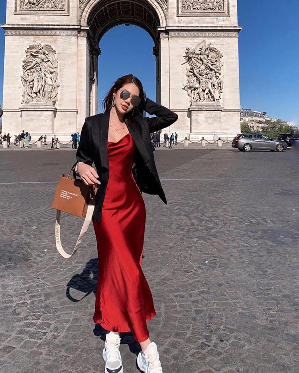 Jolie Nguyễn thể hiện sự phá cách khi chọn giầy đế khủng để mặc cùng váy lụa mềm. Cô cũng chọn kiểu áo thịnh hành để hoàn thiện set đồ dạo phố.
