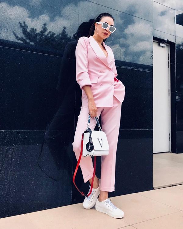 Trà Ngọc Hằng mix tông hồng trắng nhẹ nhàng cho bộ suit kiểu dáng thanh lịch đi cùng giầy đế bệt, túi hiệu tiệp sắc màu.