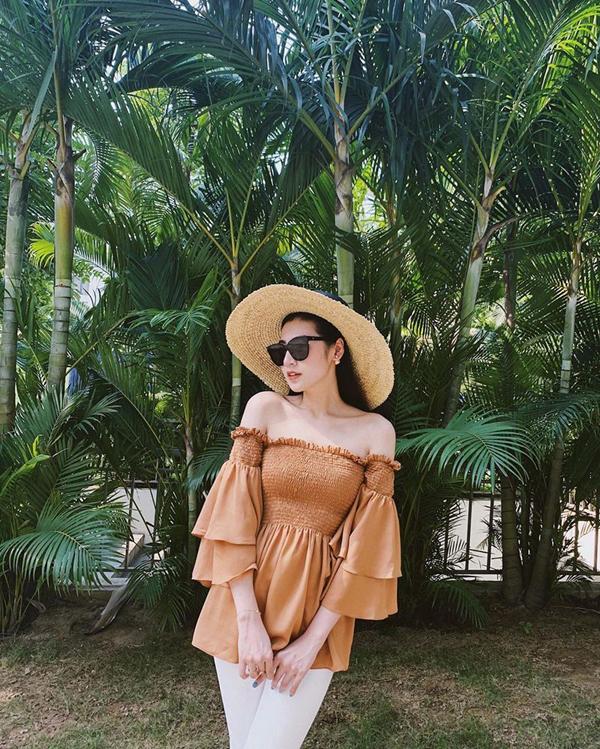 Á hậu Tú Anh thể hiện phong cách ăn mặc đúng điệu mùa hè với áo trễ vai tông màu nâu nhạt, mũ cói. Cô trung hòa màu sắc cho set đồ bằng kiểu quần skinny trên tông trắng.